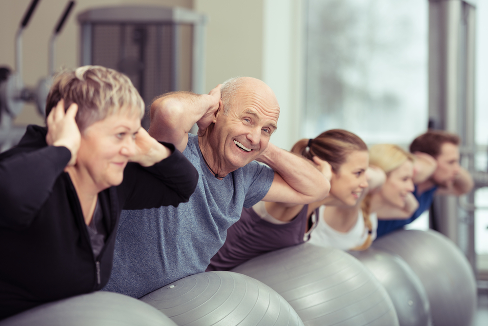 Elderly couple doing pilates class at the gym with a group of diverse younger people balancing on the gym ball with raised arms to tone their muscles in an active retirement concept