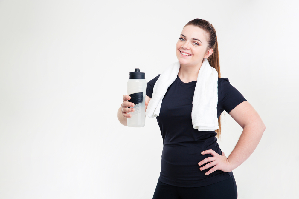 Portrait of a smiling thick woman in sportswear holding shaker isolated on a white background
